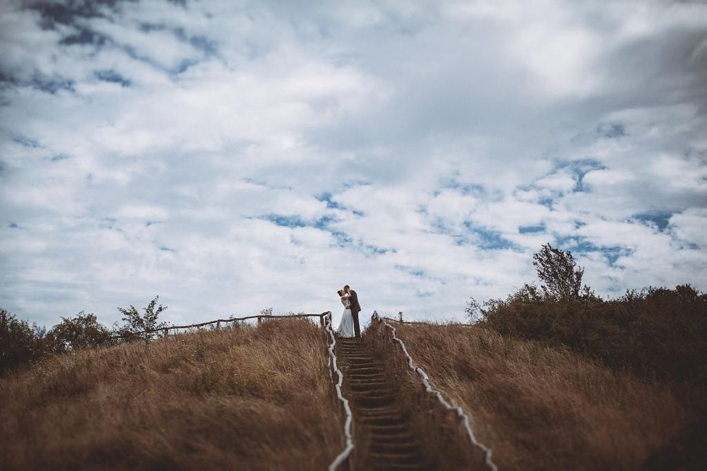 Brautpaar küsst sich Wolken Himmel